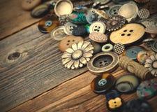 I vecchi bottoni in grandi numeri hanno sparso sui bordi di legno invecchiati Fotografia Stock