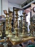 I vecchi candelieri d'ottone differenti in seconda mano del mercato delle pulci comperano Fotografia Stock