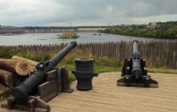 I vecchi cannoni enormi stanno sui supporti di legno contro lo sfondo di un impallidire di legno e sono puntati sulla diga idroel fotografia stock libera da diritti