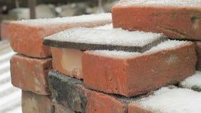 I vecchi mattoni ed altri materiali da costruzione si trovano impilato fuori della stanza sotto la neve stock footage