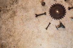I vecchi strumenti d'annata arrugginiti hanno posto pianamente su calcestruzzo sotto forma del sole Immagini Stock