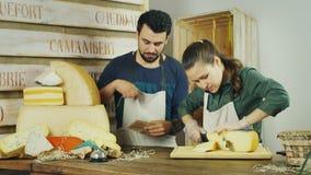 I venditori equipaggiano e donna che lavora insieme in un negozio dei formaggi archivi video