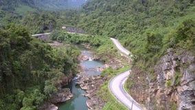 I venti della strada asfaltata lungo il piede della collina vicino al chiaro fiume basso video d archivio