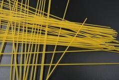 I vermicelli asciutti lunghi, spaghetti italiani della pasta dalle varietà del grano duro dentro ingrassano un fondo nero interes fotografia stock libera da diritti