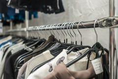 I vestiti appendono su uno scaffale in un deposito dei vestiti Fotografia Stock