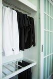 I vestiti appendono su uno scaffale in un deposito dei vestiti di progettista, gabinetto moderno con la fila dei panni che append Fotografie Stock Libere da Diritti