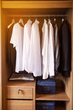 I vestiti appendono su uno scaffale in un deposito dei vestiti di progettista, gabinetto moderno con la fila dei vestiti che appe Immagini Stock Libere da Diritti