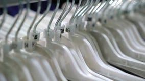 I vestiti appendono in un deposito del boutique stock footage