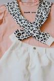 I vestiti casuali e d'avanguardia, di maglietta colorata di corallo, la maglietta felpata del leopardo ed i jeans bianchi si vest immagini stock libere da diritti
