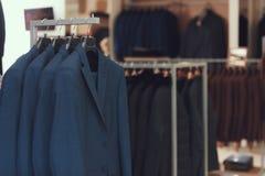 I vestiti degli uomini di affari appendono sui ganci in boutique dei vestiti di affari Grande scelta del vestito Fotografia Stock