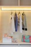I vestiti del bambino che appendono sullo scaffale con le scarpe ed i calzini Immagini Stock