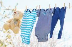 I vestiti e gli accessori del bambino pesano sulla corda dopo avere lavato all'aperto Fuoco selettivo fotografie stock libere da diritti