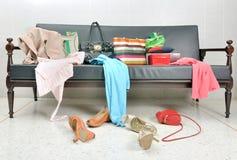 I vestiti, la borsa di signora e le scarpe sudici hanno sparso su un sofà immagine stock
