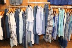 i vestiti recintano in vestiti variopinti dalle donne del negozio di vestiti sui ganci in un dettagliante Fotografia Stock