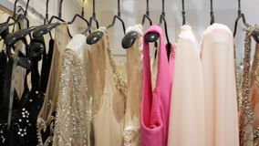 I vestiti uguaglianti di lusso appendono sui ganci nel deposito Vestiti dal lusso Vestiti da sposa 4K video 4K archivi video