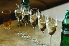 I vetri con champagne stanno in un raggio sulla tavola Immagine Stock