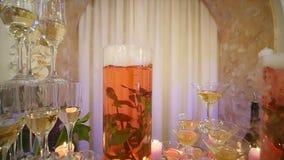I vetri con l'alcool e le bevande differenti, i bicchieri di vino ed il champagne sono sulla tavola di buffet, vino rosso in vetr archivi video