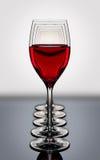 I vetri del vino rosso in una fila backlighted su un verro nero riflettente Immagini Stock