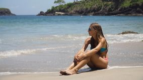 I vetri della ragazza al sole si siede sulla spiaggia Immagine Stock Libera da Diritti