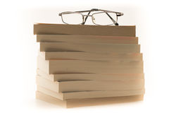Vetri di lettura sopra un mucchio dei libri Fotografia Stock