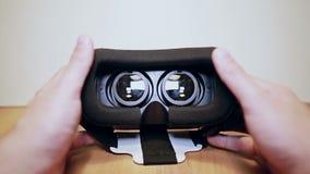 I vetri di realtà virtuale, vr sulla tavola, equipaggia le mani le prendono e dura video d archivio