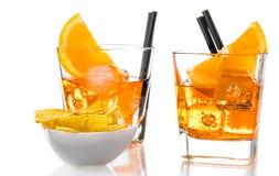 I vetri di spritz il cocktail di aperol dell'aperitivo con le fette ed i cubetti di ghiaccio arancio vicino ai chip dei taci Immagine Stock