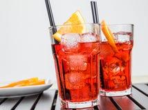 I vetri di spritz il cocktail di aperol dell'aperitivo con le fette ed i cubetti di ghiaccio arancio vicino al piatto delle aranc Immagine Stock Libera da Diritti