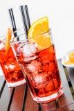 I vetri di spritz il cocktail di aperol dell'aperitivo con le fette ed i cubetti di ghiaccio arancio vicino al piatto delle aranc Immagine Stock