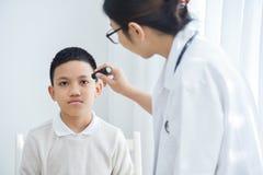 I vetri di usura di medico che controllano un paziente del ragazzino osserva immagini stock