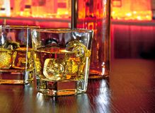 I vetri di whiskey con ghiaccio sulla barra presentano vicino alla bottiglia di whiskey su atmosfera calda Fotografie Stock
