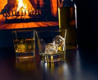 I vetri di whiskey con i cubetti di ghiaccio si avvicinano alla bottiglia di whiskey davanti al camino Fotografie Stock