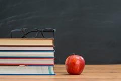 I vetri e la mela rossa con i libri sul ` s dell'insegnante istruiscono lo scrittorio Fotografie Stock Libere da Diritti
