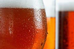 I vetri gelidi della birra fresca spumano, coperto di gocce, primo piano Immagini Stock Libere da Diritti