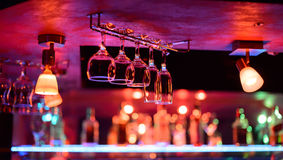 I vetri vuoti per vino sopra una barra tormentano Fotografia Stock