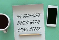 I viaggi grandi cominciano con i piccoli punti, il messaggio su carta, lo Smart Phone ed il caffè sulla tavola fotografia stock libera da diritti