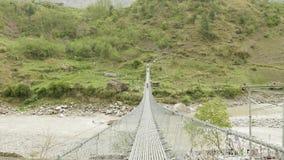 I viaggiatori con zaino e sacco a pelo camminano sul ponte sospeso sopra il fiume nel Nepal Viaggio del circuito di Manaslu stock footage