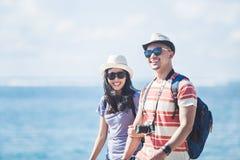 I viaggiatori con zaino e sacco a pelo coppia il cappello e gli occhiali da sole d'uso dell'estate che camminano sopra fotografia stock libera da diritti