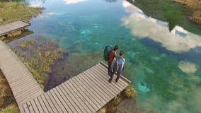 I viaggiatori con zaino e sacco a pelo delle donne stupiscono nel bello lago stock footage