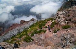 I viaggiatori vanno giù su un pendio di montagna Fotografia Stock