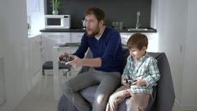 I video giochi, uomini con il figlio giocano con il regolatore del gioco nelle mani a casa