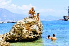 I villeggianti prendono il sole su una roccia enorme nel mare Alanya, Turchia Immagini Stock
