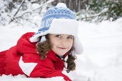 I vinter i träna i snön ligger en liten lockig flicka Arkivbilder