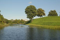 Copenhagen, Denmark - August 21,2017: Nice trees beside the river in a summer day. When I visit an old house and I sea this scene outside the house. Nice tree royalty free stock photography