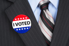 I voted pin on lapel. A male voter in his business suit wearing a vote pin on his lapel Stock Photo