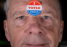 I Voted Today paper sticker on mans forehead with warm smile at camera stock photography