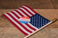 I Voted Today paper sticker on US Flag and rural wooden table royalty free stock image