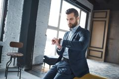 I am waiting...Bearded successful businessman is looking at his watch and waiting for important meeting. Fashion look at office. Close-up stock photo