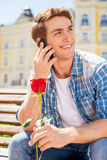 I am waiting for you!. Happy young man holding single rose and talking on the mobile phone while sitting on the bench Royalty Free Stock Photos