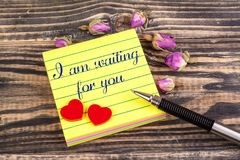 I am waiting for you note. I am waiting for you in sticky note with tow heart and dried rose buds on wood Royalty Free Stock Image