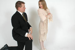 But I want. Image of a daughter with her arms crossed while the dad is on his knee's. Interaction between father and daughter Royalty Free Stock Image